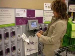First: At the Scan It rack, shopper Debra Mals scans her Stop & Shop card, then picks up a Scan It device from one of the nests.