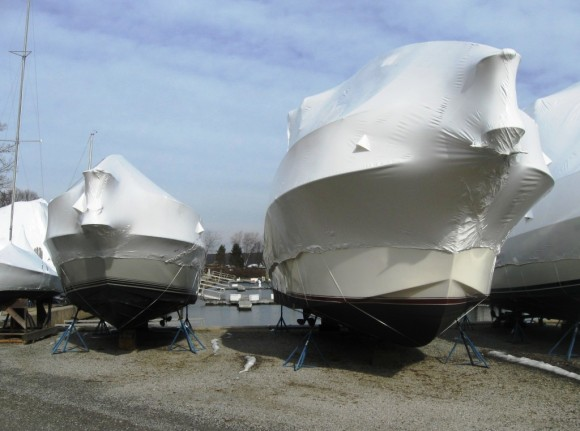 Shrink wrapped boat in winter with water slips behind them