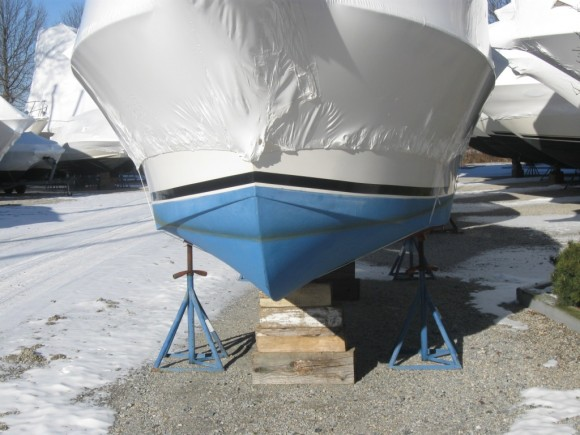 The bow of a shrink wrapped boat on wood blocks and supporting metal stands