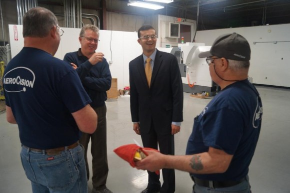 AeroCision CEO Andrew Gibson (center left) and Sen. Art Linares (center right) chat with AeroCision employees during Linares' Feb. 27 tour of the Chester-based manufacturer.