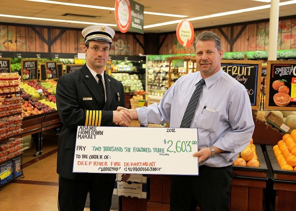 Adams Manager Jeff Prindle presents Deep River Fire Chief Tim Lee with check.