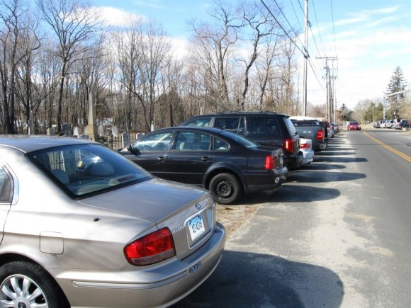 Cars parked beside the cemetery on North Main Street