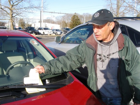 Parking Attendant Lobo puts in place a collection envelope