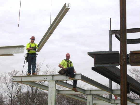 Workers precariously perched on narrow steel girders at construction site