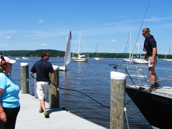 An Essex dock worker catches the sailboat's line