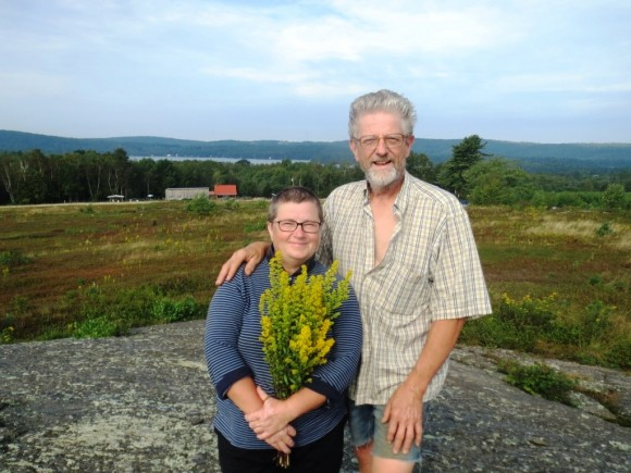 Richard and Maria on top of their new world, happy in their fields of wild blueberries.  Visible  below are their home and barn, and far back, Lake St. George. She picked the flowers on the walk up