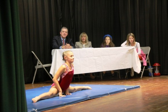 "5th Grader Addison Marchese sings ""Rockin' Robin"" while performing stunts, as Principal Jeffrey and Superintendent Levy observe"