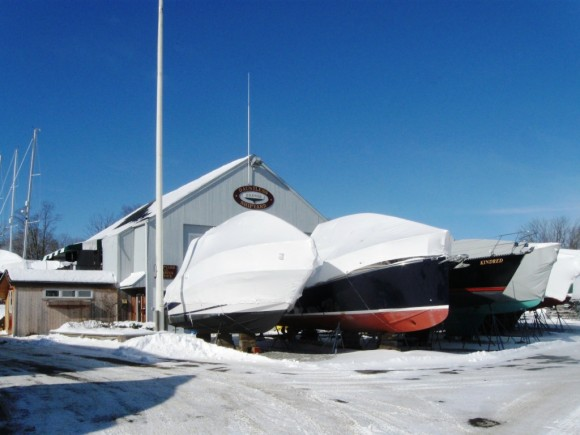 Covered boats at a shoreline boatyard unaffected by the snow