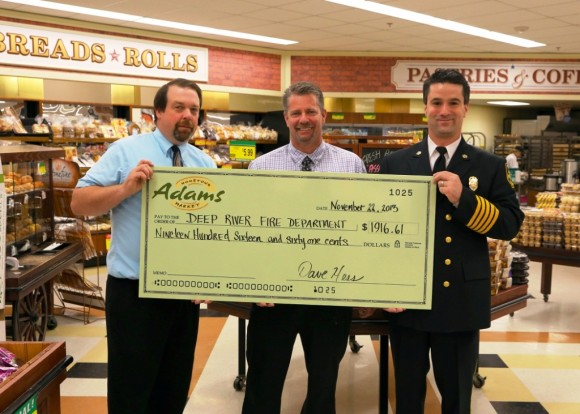 Customer Service Manager Kevin Hunt  (left) and Adams Manager Jeff Prindle present  DRFD Chief Tim Lee with a check for the Department.