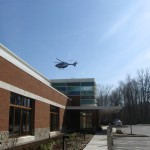 Exterior of Emergency Center with helicopter coming in
