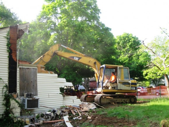 A bulldozer claws away at the old slum house
