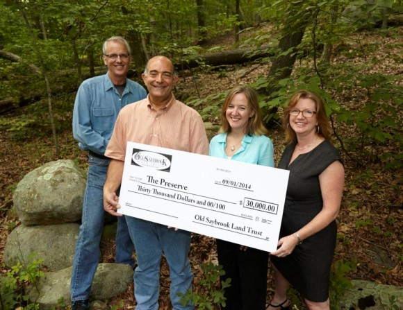 (l-r) Old Saybrook Land Trust President Joe Nochera and Treasurer Mike Urban present Alicia Sullivan and Lori Fernand (l-r) of The Trust for Public Land with a check for $30,000 toward The Preserve purchase. Photo by Bob Lorenz, taken at The Preserve trailhead on Ingham Hill Rd., Old Saybrook.