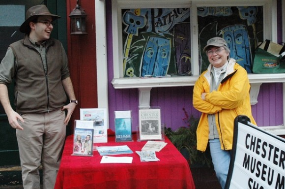 The Chester Historical Society is one of several community groups participating in the Chester Holiday Market. Here, wearing their hats for All Hat Day, are Historical Society trustees Matt Sanders and Diane Lindsay with a tableful of books and CDs about Chester for holiday gifts.