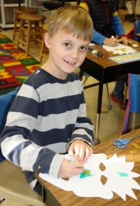 Second grader Lyle Pitman works on his Haitian mask.