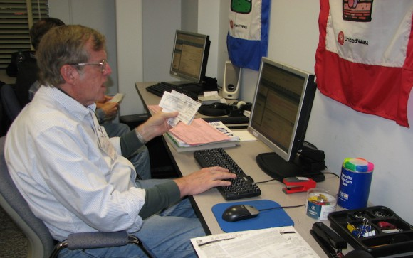 Volunteer David Morgan assists a client with taxes last year at the Volunteer Income Tax Assistance site at the Middlesex United Way office.