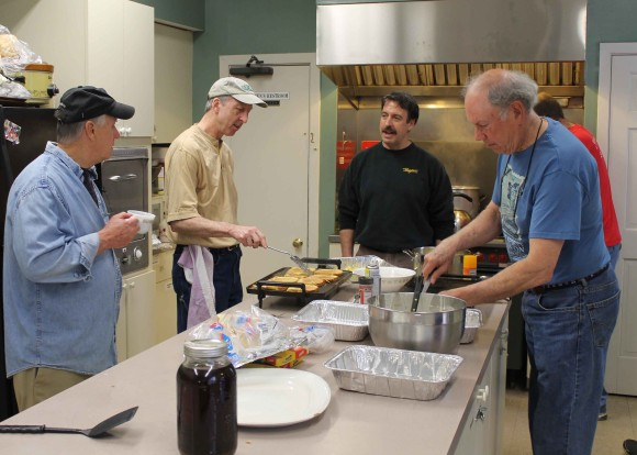 CAUTION! MEN COOKING. The men of The First Congregational Church in Essex will do all the cooking for the church's annual May Breakfast on May 9. Chefs hard at work at last year's breakfast are (l to r) Pat Callahan of Essex, Mark Foster of Ivoryton, and John Bogaert and Alan Macgregor, both of Essex.