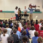 Andrew Yee of the Attacca Quartet lifts his cello over his head as the musicians describe their instruments to students at Deep River Elementary School.