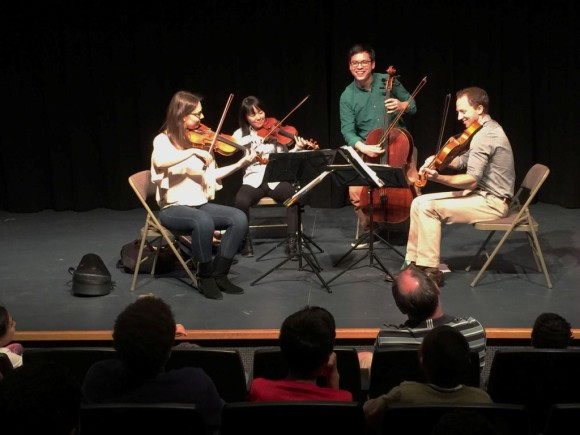 members of the Attacca Quartet take a bow after playing for students at Deep River Elementary School.