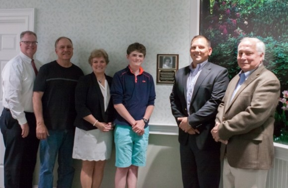 The family of Helen Shultz of Old Saybrook gathered at The Saybrook at Haddam for the unveiling of the personalized plaque to commemorate her position as Safe Harbor's first memory care resident.  Pictured here next to the plaque, left to right, are: Dan Sullivan, Richard Shultz, Judy Sullivan, Peter Sullivan, Bob Shultz, and Matthew Shultz. Two of Helen's sons, John Schultz of Staten Island, N.Y., and Mark Shultz of Mequon, Wis., were unable to attend.