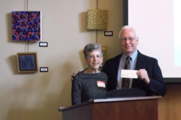 Linda Levene presents a check for $15,000 to Richard Conroy.