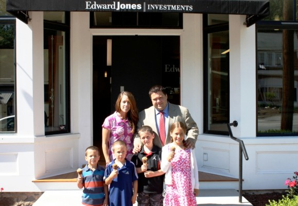 Adam Richwine stands with his family in front of the Edward Jones office in Essex, where he will be serving ice cream on July 25.