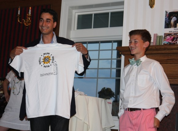 Joseph Coyne presents a Run Well t shirt from the school's 5K fundraiser to Jordan Rizza, publisher of Coastal Connecticut magazine. The magazine invited Joseph to speak at a recent VIP reception during a Grassy Strip Music Series concert, where The Country School's well project was the featured nonprofit.