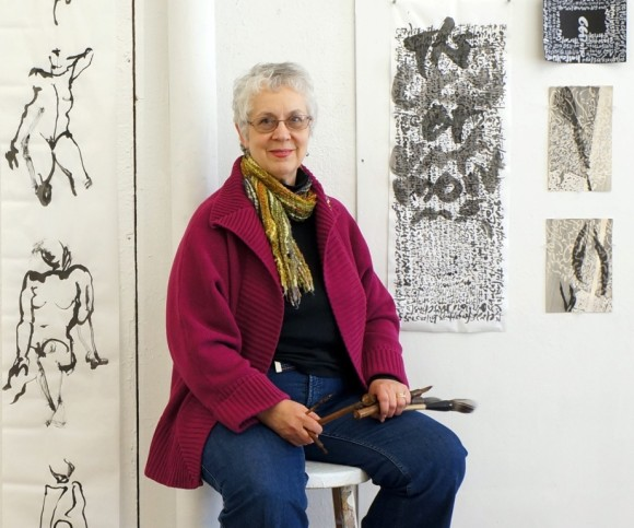Judith Barbour Osborne sits with samples of her work.