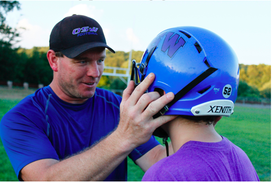 Safety Coach Jeff Miller ensures a proper fit of the top-rated Xenith helmet on an 8th grade OSW player. Photo by Michael Yermenson.