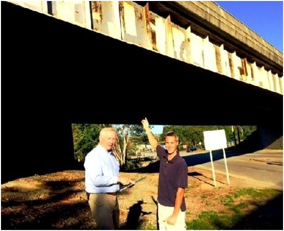Bruce Glowac and Jay Tonk, President and Vice President of the Essex Foundation, point to the bridge overpasses that they hope will be painted this spring. The Foundation has pledged $5,000 toward the $20,000 needed to repaint the overpasses.
