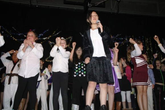 """4th grader Zoey Michel leads the entire group in a rendition of """"Glad You Came"""""""