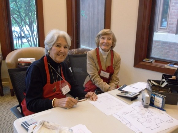 Catharine Wagner and Ellie Champion, decked in their red aprons helping patrons check out at the recent Holiday Sale.