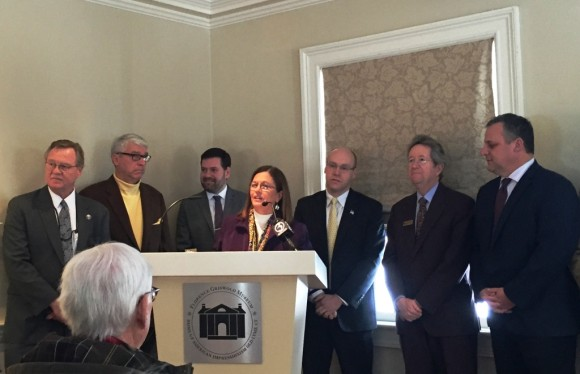 Old Lyme First Selectwoman Bonnie Reemsnyder stands at the podium at Wednesday's press conference at the Florence Griswold Museum. State officials and some of the signatories of a letter to the FRA denouncing Alternative 1 stand around her.