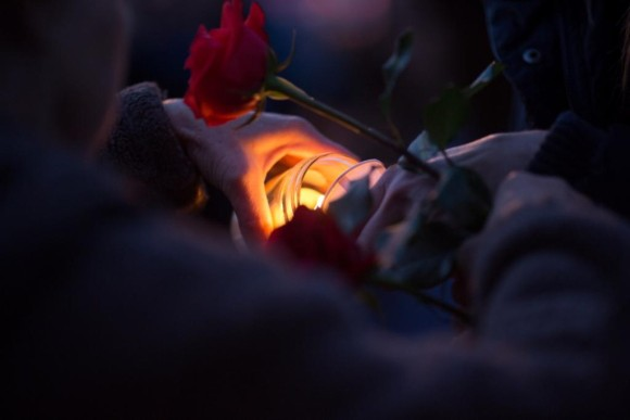 "Candles and roses are held in remembrance of Richard ""Smitty"" Smith at Monday night's vigil. Photo by Kim Tyler."