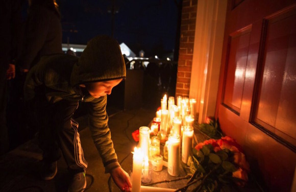 A boy sets a candle in remembrance of Deep River First Selectman Dick Smith, who passed away last Friday, March 25.