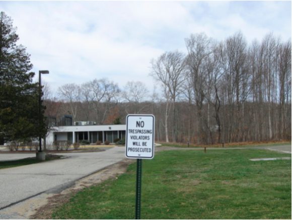 Signs threatening prosecution for trespassers stand on the grounds of Middlesex Hospital's former medical center in Essex.