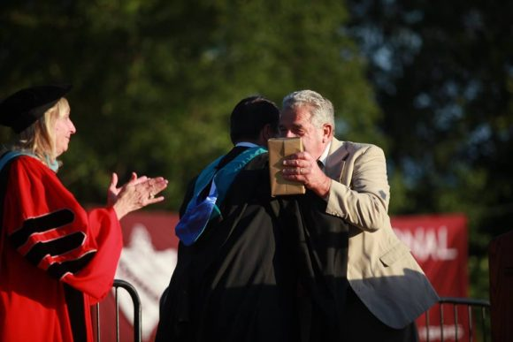 Valley Regional Principal Michael Barile hugs this year's VRHS Hall of Fame inductee.