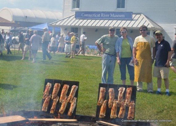 (L to R) Stephen Brinkmann, Lisa LaMonte from Guilford Savings Bank, Christopher Dobbs, and Joseph Shea watch shad roasting around the bonfire. Shad are held onto the planks with strips of salt pork, adding to their smoky flavor.
