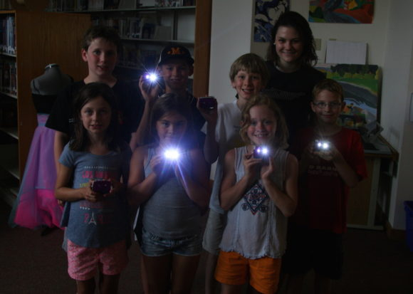 These photos show campers with flashlights, which they created in a Global Inventors camp. During the camp, students in Madison were partnered with students in Kenya, communicating about their inventions through video exchanges.
