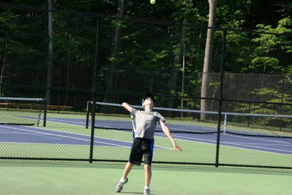 Will de Chabert, a Madison resident, Country School student, and player for Madison Racquet & Swim Club, serves during a match on one of the new Rothberg Tennis Center courts at The Country School.