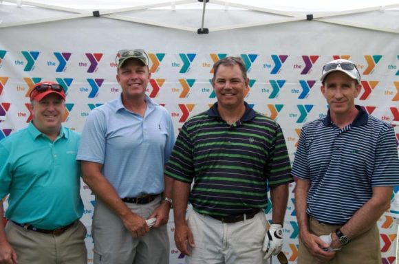 A smiling group of YMCA golf tournament winners.