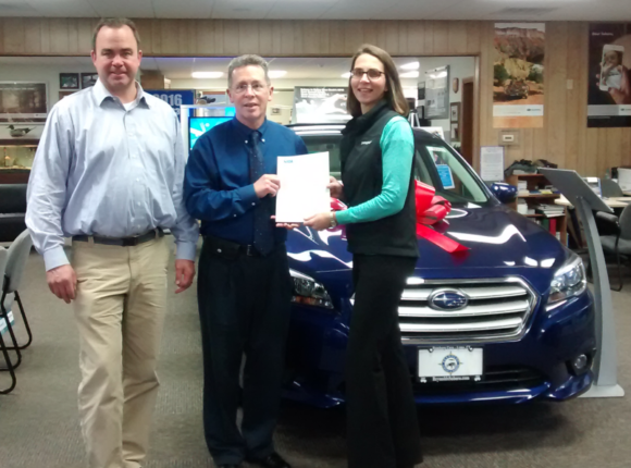 Kathryn Wayland, Owner Reynolds Subaru, is pictured presenting Paul Doyle, Estuary Council Executive Director, with a check for $1,000. Standing to the left is G. Hayden Reynolds, Owner Reynolds Subaru.